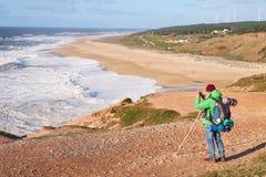 NAZARE, PORTUGAL - 1 DE FEBRERO DE 2018: El caminante masculino mira las ondas y toma imágenes de la alta orilla imagen de archivo libre de regalías