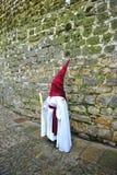 Nazarene antes de la pared de piedra, semana santa en Baeza, provincia de Jaén, Andalucía, España Fotografía de archivo libre de regalías