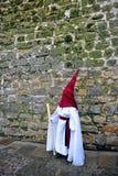 Nazarene antes de la pared de piedra, semana santa en Baeza, provincia de Jaén, Andalucía, España Fotografía de archivo