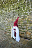 Nazarene przed kamienną ścianą, Święty tydzień w Baeza, Jaen prowincja, Andalusia, Hiszpania Fotografia Royalty Free