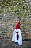 Nazarene before the stone wall, Holy Week in Baeza, Jaen province, Andalusia, Spain Stock Photography