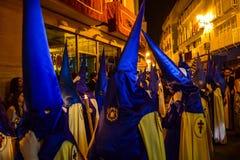 Nazarenes coloridos durante una procesión de Pascua de la tarde Fotos de archivo