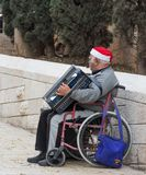 An elderly man is sitting in a wheelchair and playing the accordion in the old city of Nazareth in Israel royalty free stock photo