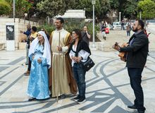 A married couple - husband and pregnant wife in the clothes of Jesus` time - stand with the attendantand guitarist in front of the. Nazareth, Israel, December 23 stock photography