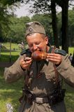Nazi eats a pork foot Stock Photography