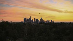 Sun falls on Los Angeles skyline as a blimp flies above downtown stock video footage