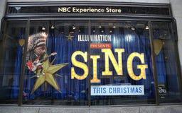 NBC经验商店窗口显示装饰与由在洛克菲勒中心的照明娱乐唱影片促进 库存图片