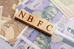 NBFC in houten blokletters op Indische munt stock foto