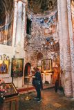 NBikortsminda, Geórgia - 28 de abril de 2017: A mulher reza no interior e nos fresco murais na catedral de Nikortsminda em Racha, Fotografia de Stock