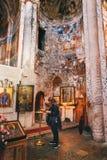 NBikortsminda, Georgia - 28 aprile 2017: La donna prega nell'interno e negli affreschi murali nella cattedrale di Nikortsminda in Fotografia Stock