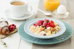 Bowl of muesli with yoghurt strawberries and blueberries boiled egg orange juice croissant and coffee for healthy breakfast stock image
