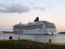 NCL Cruiseship leaves Honolulu Harbor at Dusk Stock Photo