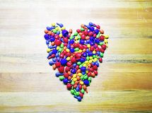 Colorful heart ove, valentin`s. Ncolorful heart icon on a wooden background stock photo