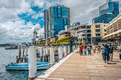 Streetview of King street wharf with people and modern international tower buildings in background in Sydney NSW Australia royalty free stock image