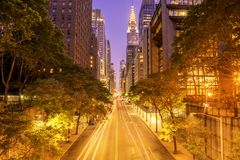42nd street Manhattan at dawn. 42nd street, Manhattan viewed from Tudor City Overpass at night featuring car light trails on the foreground stock photo