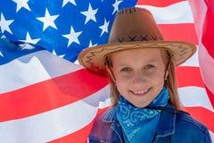 ndependencedag H?rlig lycklig flicka med gr?na ?gon p? bakgrunden av amerikanska flaggan p? en ljus solig dag En flicka i a arkivfoton