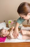 Ändernde Windel der Mutter des entzückenden Babys Stockfotografie