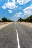 Ändlös väg med blå himmel Arkivfoto