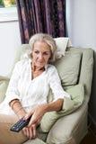 Ändrande kanaler för hög kvinna med fjärrkontroll på fåtöljen hemma Arkivfoton