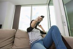 Ändrande kanaler för kvinna, medan hålla ögonen på TV på soffan hemma Arkivfoton