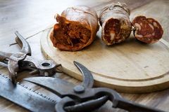 Nduja and soppressata salami with old working tools. Nduja and calabrese soppressata near old utensils of work stock image