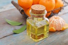 Nödvändig olja för tangerin i en glasflaska Arkivfoto