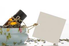 Nödvändig olja, tömmer etiketten inom ett tappningtenn och lavendelflöde Royaltyfri Fotografi