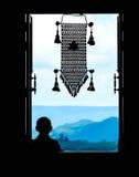 Neófito en la ventana (en silueta parcial) con el MES colgante tailandés Foto de archivo libre de regalías