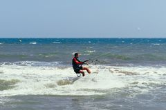 NE DE MUI, VIETNAM - 4 DE MARZO DE 2017: El kitesurfer masculino se mueve en el tablero en las ondas del mar Fotos de archivo libres de regalías