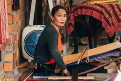 NE DE MUI, VIETNAM - 6 DE MARZO DE 2017: Tejedor de sexo femenino que trabaja en los telares tradicionales para la seda imagen de archivo