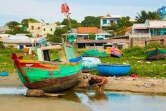 NE MUI, ВЬЕТНАМ - 02 11 2017: Рыболов очищая шлюпку на пляже на рыбацком поселке, Ne Mui, Вьетнаме Стоковые Изображения