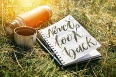 Ne regardez jamais le mot en arrière écrit dans le carnet blanc avec le stylo et un thermos rouge de tasse sur l'herbe verte Écri image stock