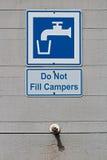 A ne remplissent pas campeurs faisant attention au signe près d'un robinet photographie stock libre de droits