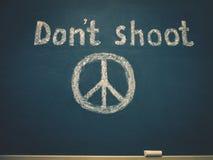 Ne tirez pas et le symbole de la paix est écrit sur le conseil pédagogique photos stock