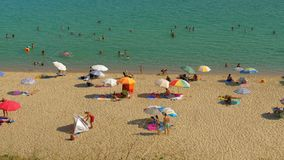 People enjoying summer vacation on the coast, Greece. Nea Kallikratia, Greece - August 12, 2017: beach with people sunbathing, relaxing under sun umbrellas and stock footage