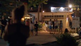People walking in the street of night Nea Kallikratia Greece. NEA KALLIKRATIA, GREECE - AUGUST 12, 2017: Families and young people walking in town street in stock video