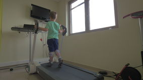 In Nea Kallikratia, Greece in clinic little boy slowly walks on the medical treadmill. Wellness treatment stock video footage