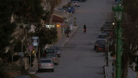 In Nea Kallikratia, Greece seen quiet street with parked cars and trees. In the distance crossing road a young family with little son stock footage