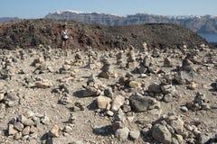 Nea Kameni volcano. A tourist looks at piles of rocks created by visitors to Nea Kameni, the volcano in the caldera at Santorini, Greek Islands Royalty Free Stock Image