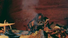 Neanderthalmannen läser den gamla boken nära brasa i hans grotta stock video