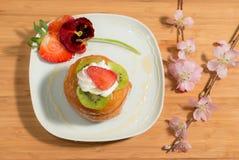 Neapolitan επιδόρπιο που διακοσμείται με το μέλι, κρέμα, φρέσκια φράουλα, άνθος αμυγδάλων και pansy Στοκ Φωτογραφία