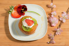 Neapolitan dessert  decorated with honey,cream,fresh strawberry,almond blossom and pansy. Stock Photography