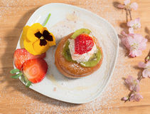 Neapolitan dessert sprinkled with icing sugar and decorated with almond blossom,pansy and fresh fruits. Royalty Free Stock Images