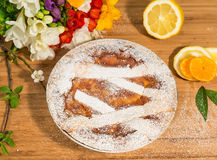 Neapolitan easter pie sprinkled with icing sugar and decorated with freesia and fresh fruits. Royalty Free Stock Image
