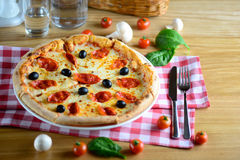 Neapolitan hot pizza with pepperoni, mozzarella, cherry tomatoes and black olives, served on a wooden table for. Italy food. Stock Image