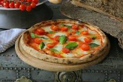 Neapolitan pizza med mozzarellaen, den körsbärsröda tomaten och ny basilika Royaltyfria Bilder