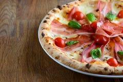 Neapolitan pizza z bekonem, mozzarellą, czereśniowymi pomidorami i kremowym kumberlandem słuzyć na drewnianym stole dla gościa re Obraz Stock