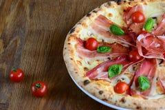 Neapolitan pizza z kremowym kumberlandem, bekon mozzarella i czereśniowi pomidory, słuzyć na drewnianym stole dla gościa restaura Fotografia Royalty Free