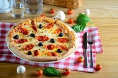 Neapolitanische heiße Pizza mit Pepperonis, Mozzarella, Kirschtomaten und schwarze Oliven, diente auf einem Holztisch für Italien Stockbild