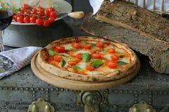Neapolitanische Pizza mit Mozzarella, Kirschtomate und frischem Basilikum lizenzfreie stockbilder